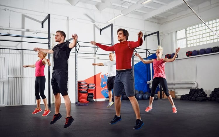 Group of people doing jumping jacks at gym