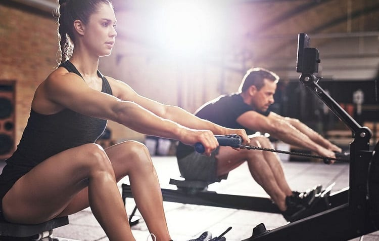 young couple train on rowing machine