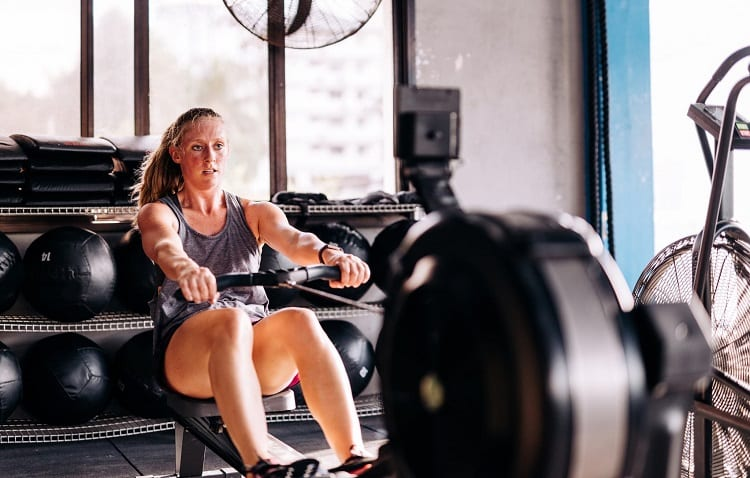 young sporty woman on rowing machine