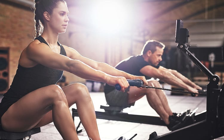 young couple on rowing machines