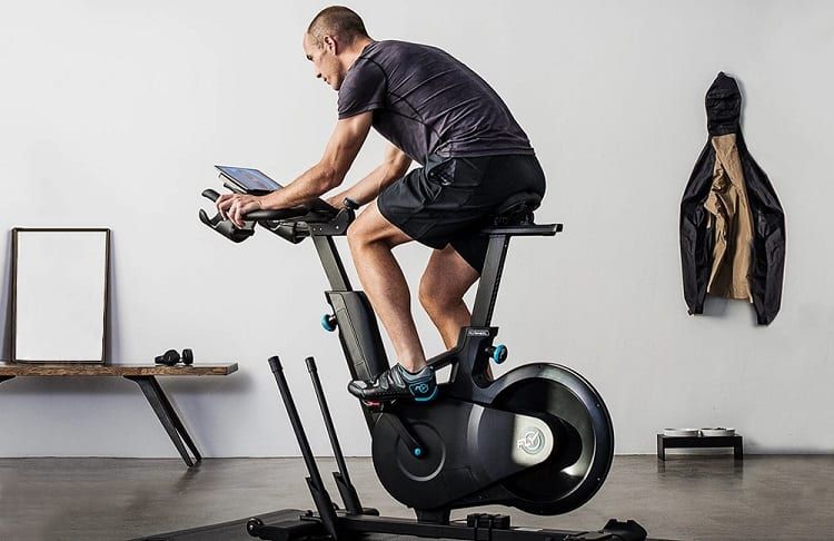 young fit man on exercise bike