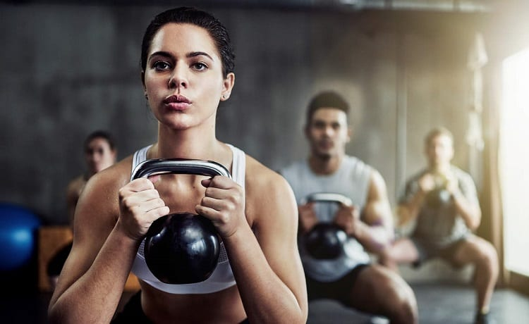 fit young woman with kettle bell at the gym